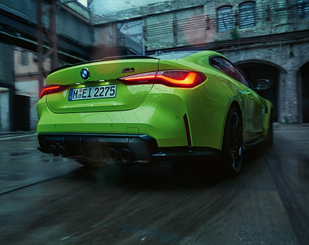 Rear end view of the All-New BMW M4 driving down a road